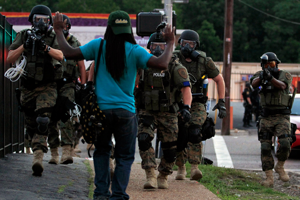 The police approach an unarmed protester in Ferguson, MO