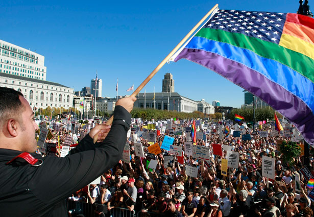 Alexander Sanchez wabes a raindow colored flag to a crowd of supporters of same-sex marriage